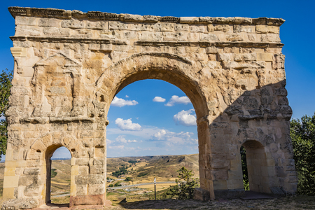 Close-up of Roman arch and back the village of Medinaceli. Soria Spain.