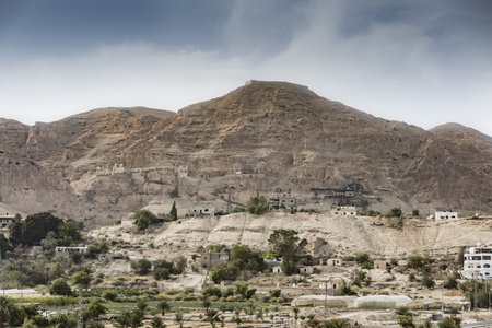 Mount of temptation with the monastery of the same name and the countless excavations on it made thousands of years before Christ. Jordan Valley West Bank Palestinian Stock Photo