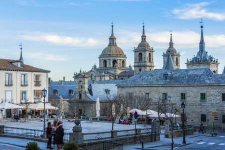 Main square of the city of San Lorenzo del Escorial and in the background the monasterys domes.