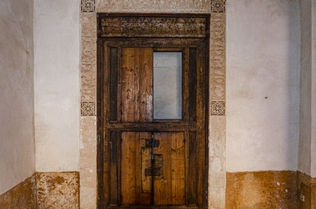 old and rustic Arabic wooden door with arabesque frame worked in stucco. marrakesh morocco