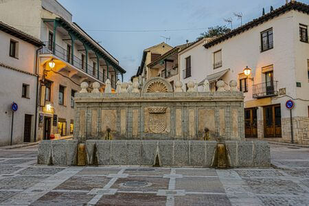 Old fountain with emblematic shields of the town of Chinchon in the main square. Madrid's community. Spain.