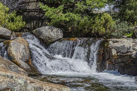 Small waterfall surrounded by rocks in the Sierra de Guadarrama. Madrid's community. Spain Foto de archivo
