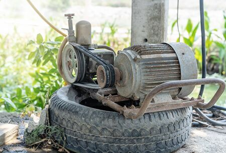Old electric motor pumping machine on a black car wheel using for farming or gardening in the house with green background at summer sunrise. The idea for technology and facilities in agriculture. Stockfoto