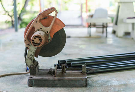 Close up of metal grinding machine or old circular saw with blurred metals on the floor, soft focus, or selective focus steels. Home improvement tools and Repair maintenance concept