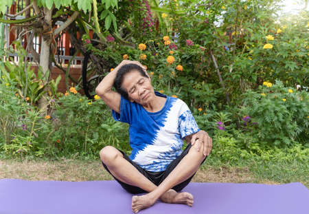 Senior old woman warming stretching exercising on yoga mat outdoor on nature green background. Happy mature or elderly lady relaxing and enjoying warmup workout. Fitness and healthy lifestyle concept