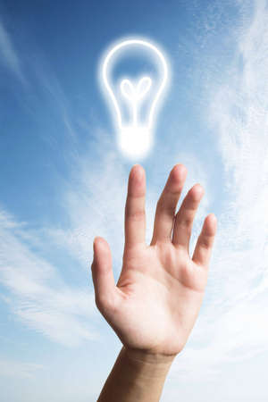 light bulb glowing on hand over blue sky Stock Photo - 7772000