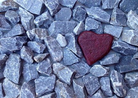 Red stone heart between many gray grit