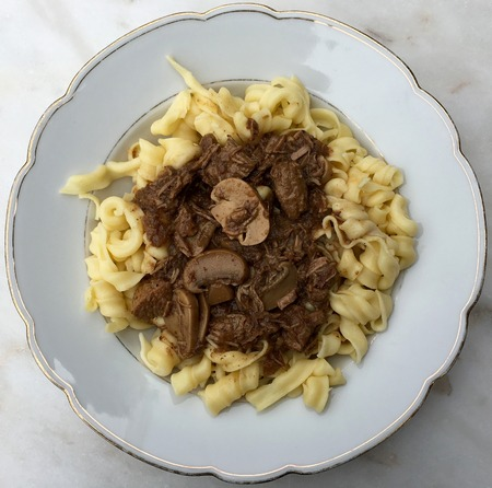 High angle view of beef goulash with mushrooms and noodles served on white plate