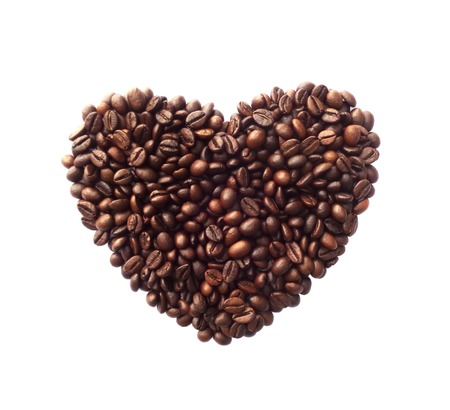 Heart shape made from coffee beans on white background
