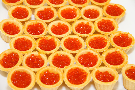 expensive food: Tartlets with salmon caviar, table decorations, fish a delicacy, caviar, red fish, salmon ROE. Expensive dish with food. Seafood. The luxurious table. The background and texture. Salty caviar.