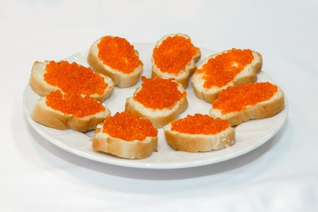 expensive food: Sandwiches with red caviar. The table decorations, fish a delicacy. Salmon ROE. Expensive dish with food. Seafood with salty caviar.