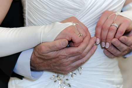 obedient: Hands of elderly bride and groom together. Old newlyweds. Wedding elderly men and women. Love all age are obedient.