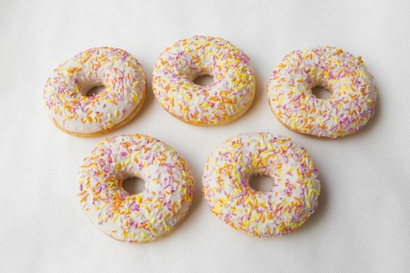 promotes: Tasty doughnut for tea. Donuts stacked slide. Food cakes delicious classic: fried doughnuts glazed with caramel. Nutritious dish that promotes obesity.