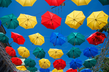 wind blown: Alley flying umbrellas. Colorful umbrellas in the sky. Fun and bright. Joy and happiness, salvation from the rain.