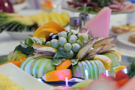 Cantaloupe: Fruit platter for dessert. Pineapples and kiwi fruit sliced and arranged in a glass vase. Fruit and juice in a carafe on the table for guests.