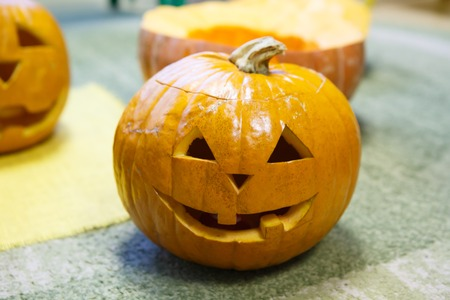 Head of a smiling Pumpkin for Halloween. Holiday is celebrated October, eve of all saints Day. Trappings of Halloween in a pumpkin head with a candle inside. Main symbol of holiday is Jack-o-lantern.