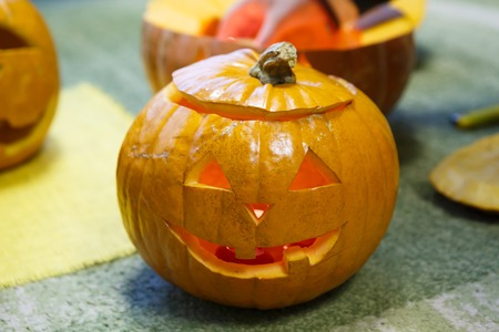 Head of smiling Pumpkin for Halloween. Holiday is celebrated October, eve of all saints Day. Trappings of Halloween in a pumpkin head with a candle inside. Main symbol of holiday is Jack-o-lantern.