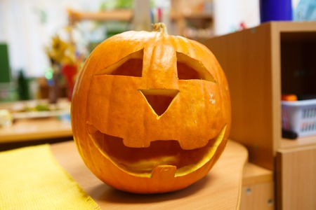 Head smiling Pumpkin for Halloween, eve of all saints Day. Trappings of Halloween in a pumpkin head with a candle inside. Main symbol of holiday is Jack-o-lantern.