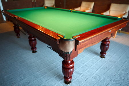 billiards room: Pool table from natural slate covered with green cloth. The movement of the balls with the cue - male fun.
