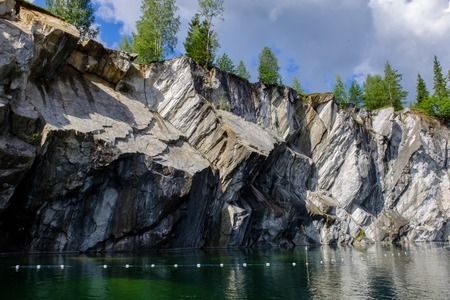 occurrence: Occurrence of white and grey marbles. Stone cliff going into the water. Landscape of mountains and sky.