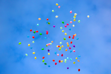 Balloons are flying in the blue sky.