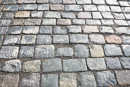 The background of the cobbled paved stone road.