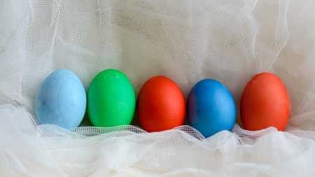 Fun colored eggs painted manually. Handmade food on a subtle texture.