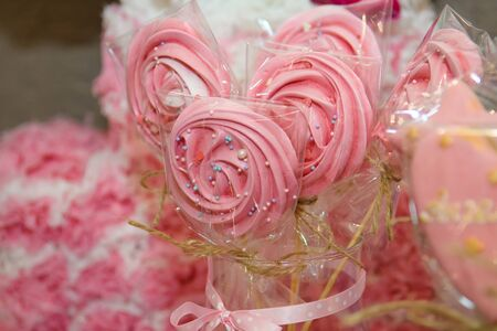 Shaped pink colored lollipops.