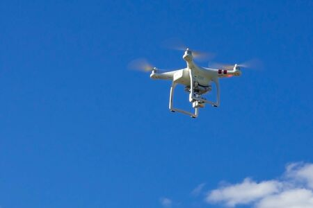 Quadcopter flies in the blue sky.