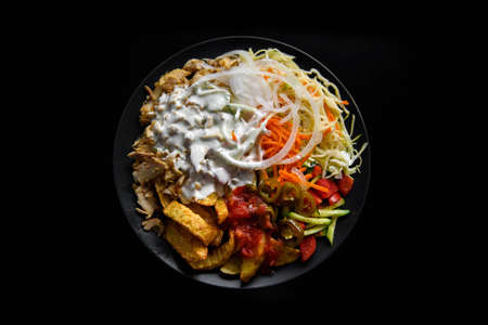 Dish with Asian food on black background.