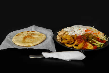 Serving Asian food with flatbread on a black background.