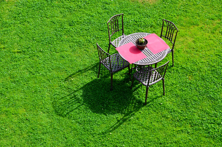 iron garden table and chairs on green grass