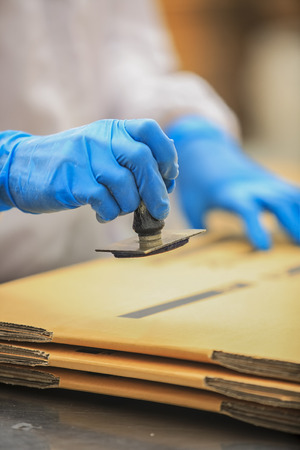 quality check: workers knot rubber stamp on the box. Stock Photo