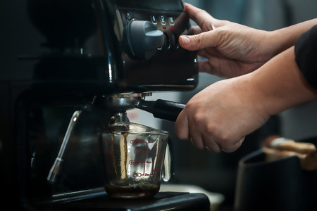 portability: espresso machine with hand in processing coffee drink Stock Photo