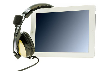 Tablet computer with headphones on a white background