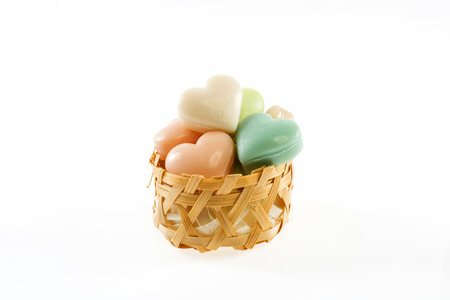 Collection of heart shaped soaps in wicker basket isolated on white background photo