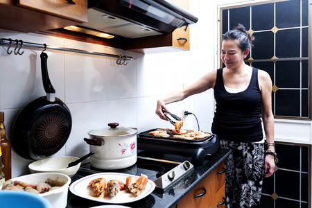 sizzle: Asia woman is grilling shrimp in the kitchen