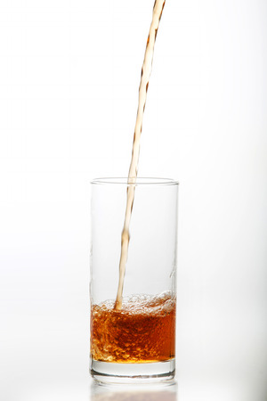 english ethnicity: Iced Tea pouring splash into a glass  isolated on white background