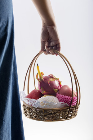 Woman hand carrying a shopping basket full of fruits. isolated on white background photo