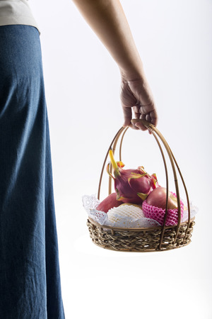Woman hand carrying a basket full of fruits. isolated on white background photo