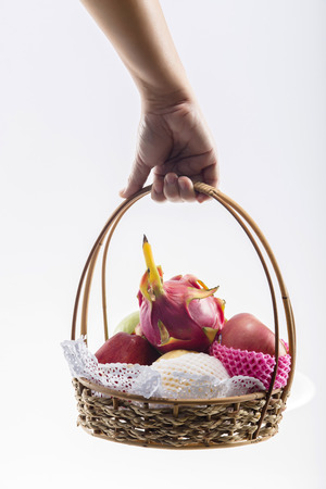 Hand carrying a basket full of fruits. isolated on white background photo