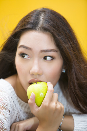 dentalcare: Close up of asian girl being about to bite an green apple Stock Photo
