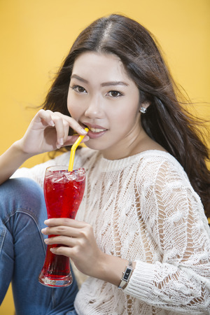 clear away: Young asian woman drinking Red tropical drink by straw Stock Photo