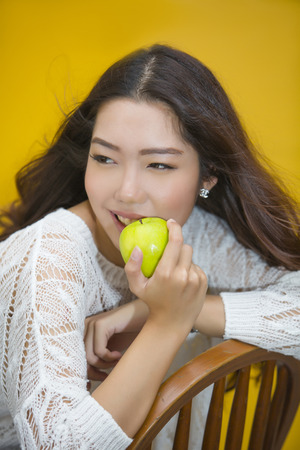 pleasantness: Happy asian woman eatting green apple on yellow background Stock Photo