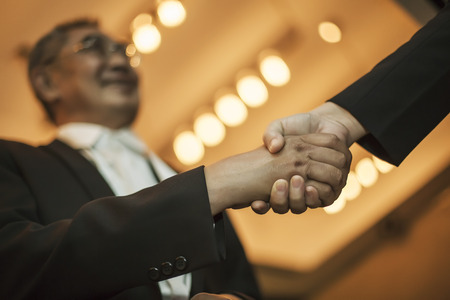 ovation: Two Asian businessman shaking hands