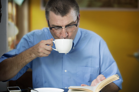 cafeteria: Man Drinking And Reading Book In Cafeteria