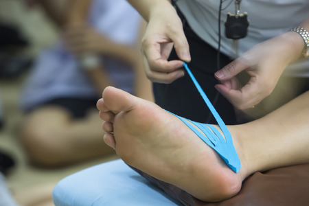 physical test: A physiotherapist is applying tape to a patients foot