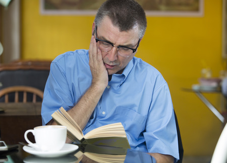 concentrated: man caucasian reading concentrated in a cafe