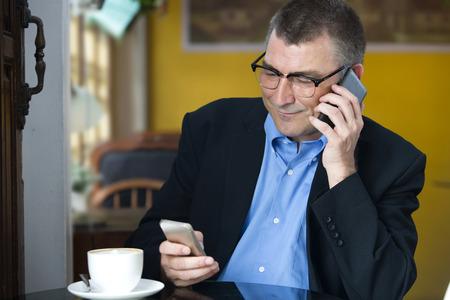 person sitting: Retrato de hombre de negocios mayor que se sienta en el caf� mientras que hace la llamada y la celebraci�n de tel�fono m�vil en la mano. La gente de negocios en el trabajo.