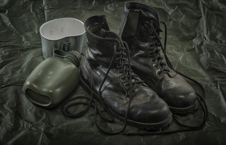 Old combat boots and military canteen on military Canvas  background